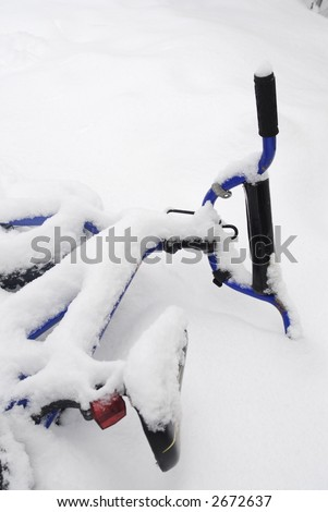 A blue kids bicycle is covered in snow.