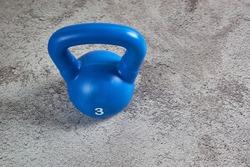 A blue 3 kilogram cast iron weight on a gray soft carpet surface