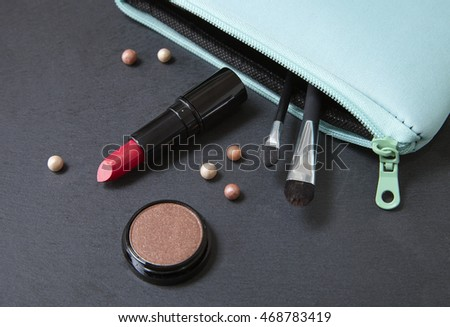 A blue make up bag with beauty products spilling on a dark slate background #468783419