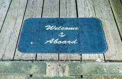 A blue mat on a wooden boardwalk reads welcome aboard with a ships anchor embroiderd on.