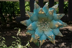 A Blue Metal Blossom Ornament in the Garden