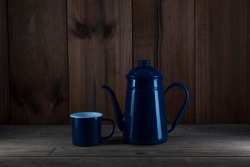 A blue metal kettle on a wooden floor and a blue metal cup.