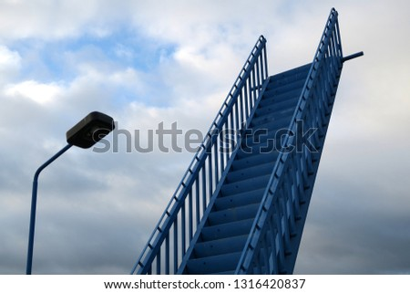 a blue metal stairway seems to lead to the heaven but it is an old stairway of a ferry pier in Sassnitz on the baltic sea