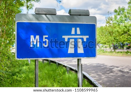 A blue motorway sign directs drivers and traffic onto the M5 motorway in England, United Kingdom. #1108599965