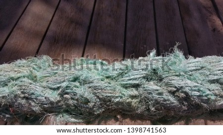 A blue old sailor rope and the woody background #1398741563