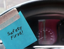 A blue paper note sticking on the car steering wheel, with text written SAFETY FIRST, to remind the driver to drive carefully and avoid distraction while on the road.