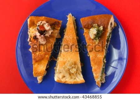a blue plate on a red background with three slices of tiella pies from Gaeta with different fillings