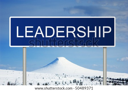 A blue road sign with white text saying Leadership