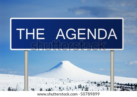 A blue road sign with white text saying The Agenda