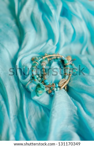 a blue scarf is feminine bracelet of small colored beads