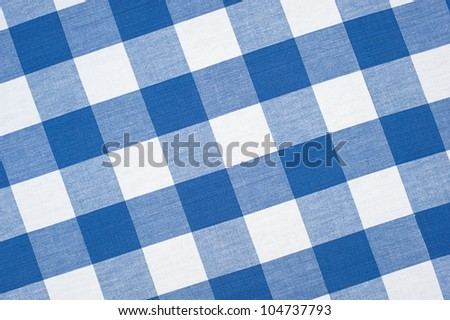 A blue, seamless, checkered picnic tablecloth fully framed with a diagonal perspective. - stock photo