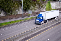 A blue semi truck with day cockpit and a roof spoiler to reduce air resistance and improve aerodynamics carries the trailer with cargo along the road in an urban city area