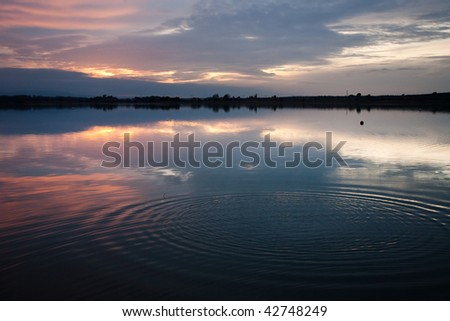 A blue sky with clouds reflected on a lake surface