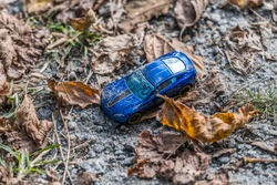 A blue small toy car laying on the ground covered with dirt and sand surrounded by fallen leaves left and forgotten along the trail in a park on a sunny day in autumn