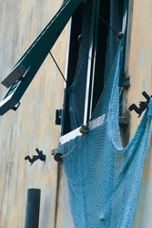 A blue textured fishing net hanging on the open window; shabby wall; Italian lifestyle