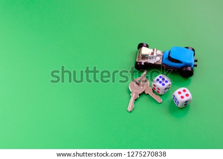 A blue toy car, a $ 100 bill rolled up into a roll; two keys on a green background. The concept can be used to promote world institutions. Symbolic objects. #1275270838