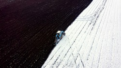 A blue tractor plows a field covered with snow. Behind the tractor is black earth. The edge of the field, start. Russia, Ural, Aerial View