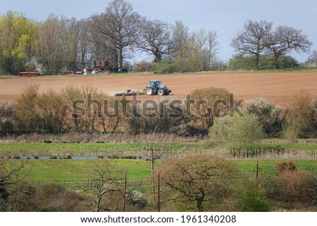 A blue tractor smoothing the ground in a farm with trees and grass around Foto stock ©