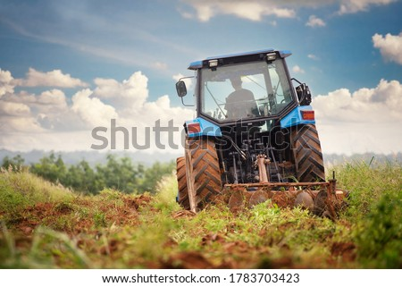 A blue tractor working on farm land Photo stock ©