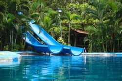 A blue water slide reflecting in the blue pool water with some green palm trees in the background in a hot springs water park at Arenal Volcano in Costa Rica.
