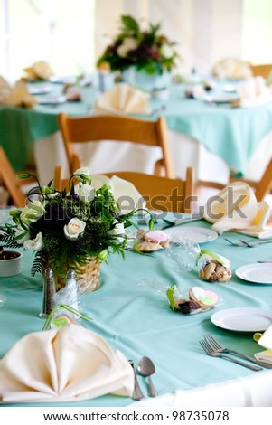 a blue wedding table with cookie favors and flower centerpieces