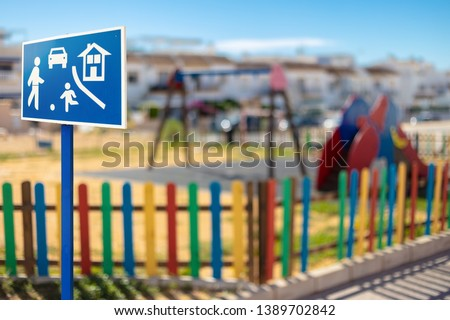 A blue white signboard indicating a game road with a playground with swing, slide and a colorful fence in the background, the sky is blue with sunshine. #1389702842