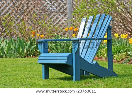 A blue wooden lawn chair in the spring garden.