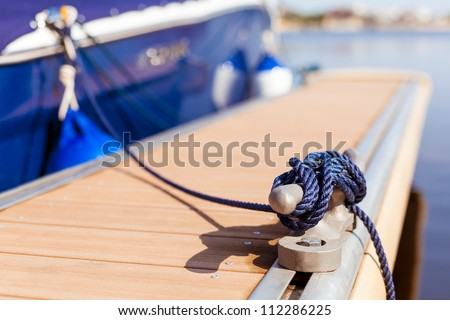A blue yacht moored with a line tied around a fixing on the quayside/ Mooring at a pier