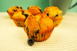 a blueberry berry and five muffins with blueberries, pea flour, rice flour, eggs and yogurt stand in front of a turquoise mug on a white surface with a turquoise wall on the side . homemade cakes