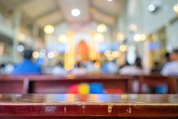 A blurred background photo of the inside of a Vietnamese church sanctuary that is filled with people in the pews, and the pastor stands under a large cross at the altar, in Vietnam. Selective focus.