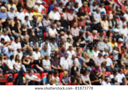 A blurred crowd of spectators in a stadium at a sporting event.