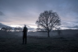 A blurred ghostly figure in the countryside on a moody atmospheric winters evening.