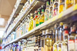 A blurred image of a supermarket shelf with alcoholic beverages.