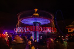 A blurry colorful carousel in motion at the amusement park, night illumination. Long exposure.