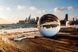 A blurry Toronto skyline behind a lensball with its reflection at Polson Pier as the sun is setting on a cold winter day.