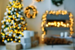 A blurry view of the stylish interior of a Christmas room in a bright room with lights garlands.