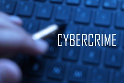 A bluured background of man pointing a pen on a keyboard, shallow depth of focus with 'CYBERCRIME' written on it.Digital Business and Technology concept.