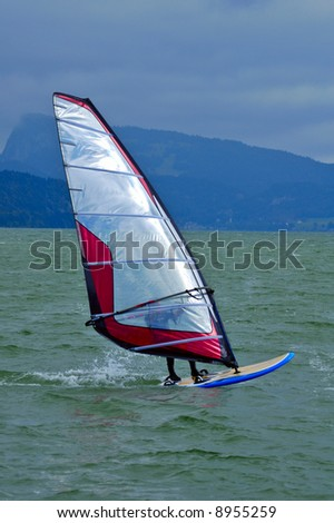 A board sailor on a mountain lake, with a storm developing. Space for text in the sky.