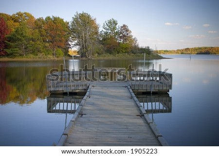 A boat dock overlooks a tranquil, fall lake scene