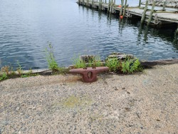 A boat docking station, or a cleat, that is used to tie up boats to keep them attached to the pier. Its metal, red, and in the shape of a letter T. The wharf is wooden and zig zags.