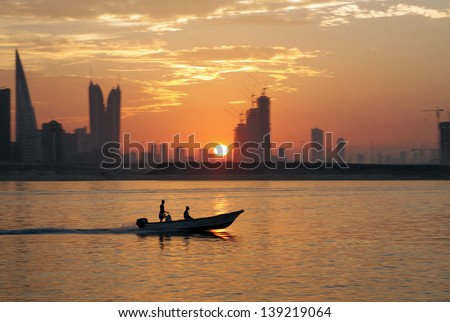 A boat during sunset with Bahrain highrise buildings