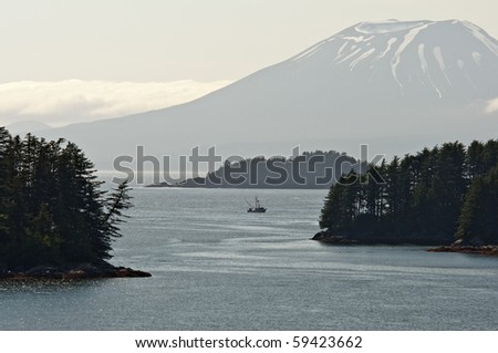 A boat fishes in Sitka Sound under Mount Edgecombe, Alaska.