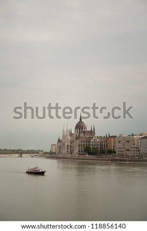 A boat floating by the Parliament Building in Budapest, Hungary