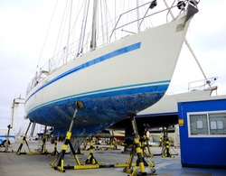 A boat in a boatyard, pleasure sailing craft supported on the hardstand, annual boat maintenance.