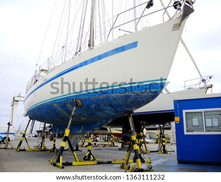 A boat in a boatyard, pleasure sailing craft supported on the hardstand, annual boat maintenance. #1363111232