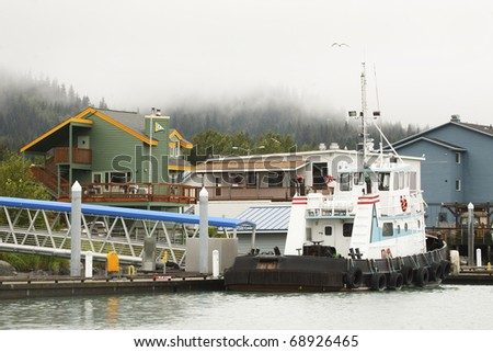 A boat in the harbor of a small town in Alaska.  There are colorful buildings in the background, and pine trees surrounded by mist and fog.