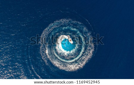 A boat is driving in a circle and produces a big whirlpool