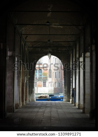 A boat on a canal seen through an archway in Venice, Italy.  Venice is famous for its canals, which are used instead of roads for transport throughout the city.   #1339891271
