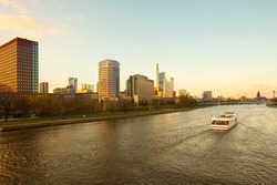 A boat on River Main in front of city skyline of Frankfurt, Hesse, Germany