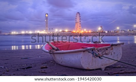 A boat on the beach at the end of the day after bad weather with the great mosque of Algiers and a big wheel in the background Foto stock ©